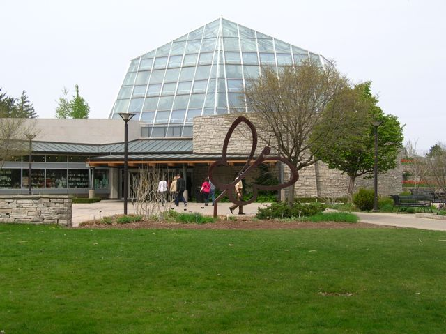 A large metal butterfly sculpture in front of a high glass dome