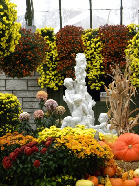 White marble fountain featuring little babies with yellow, orange mums