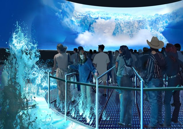 People standing on a grid platform spouting water upwards while they watch a huge surround screen featuring the falls.