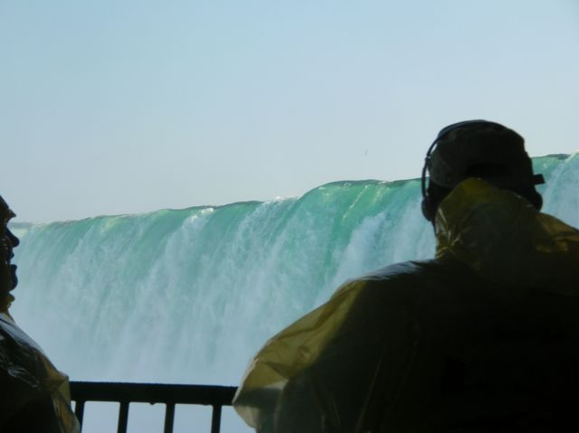 Two silhouettes and the green crest of Canadian Falls above them