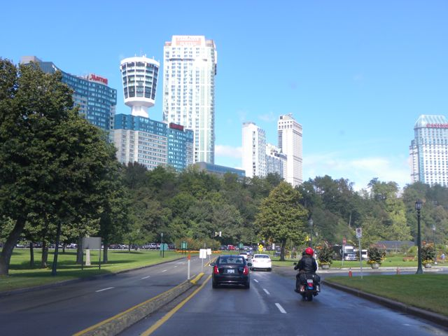 A line of huge white hotels under a blue sky with a bank of green trees beside the roadway