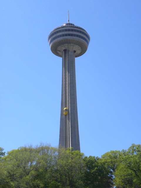 Tower with circular structure on top and yellow exterior pod elevator one-third the way up to the top