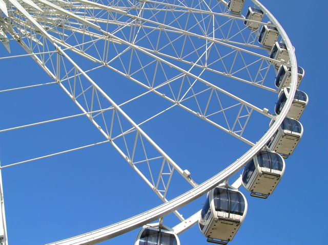 Section of metal ferris wheel with pods against a briliant blue sky