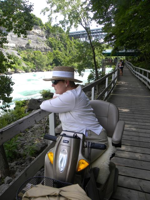 Linda on her scooter on a long wooden boardwalk beside the rapids