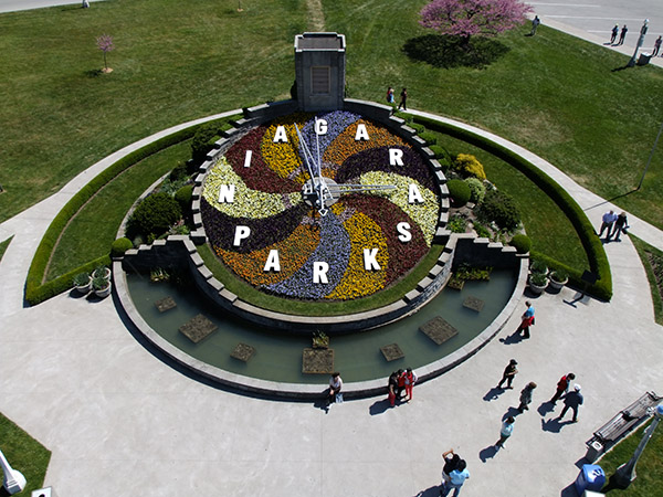 Overhead view of the floral clock saying Niagara Parks and surrounding garden with people sitting on its concrete lip