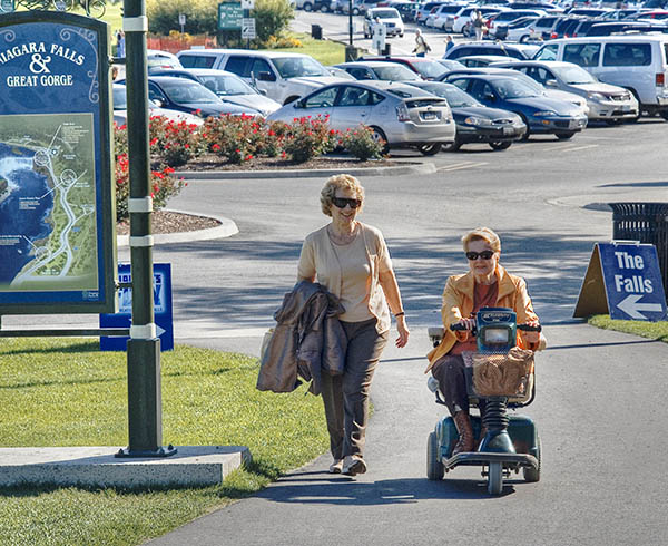 Eileen walking and Linda on her scooter outside smiling and chatting as they go along a path past a sign saying Niagara Falls and Great Gorge and another sign with an arrow pointing to the Falls